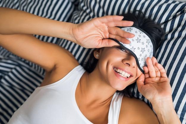 Ritratto di giovane donna attraente bruna sdraiata sul letto in pigiama e maschera per dormire, sorridente in camera da letto, emozione felice, pigro al mattino, sveglia, denti bianchi Foto Gratuite