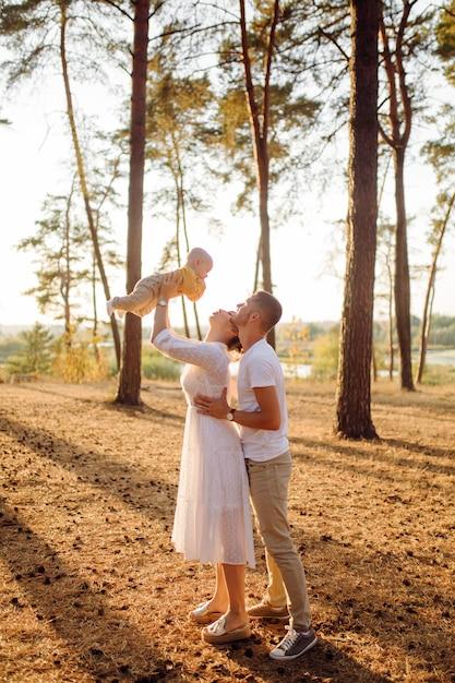 Ritratto di giovane famiglia attraente con figlio piccolo bambino, in posa nella bellissima pineta autunno al giorno pieno di sole. bell'uomo e la sua bella mora moglie Foto Gratuite