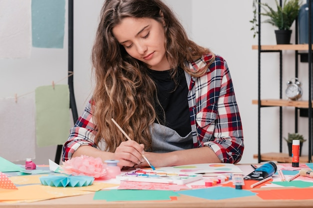 Portrait of a young attractive female artist painting on paper Free Photo