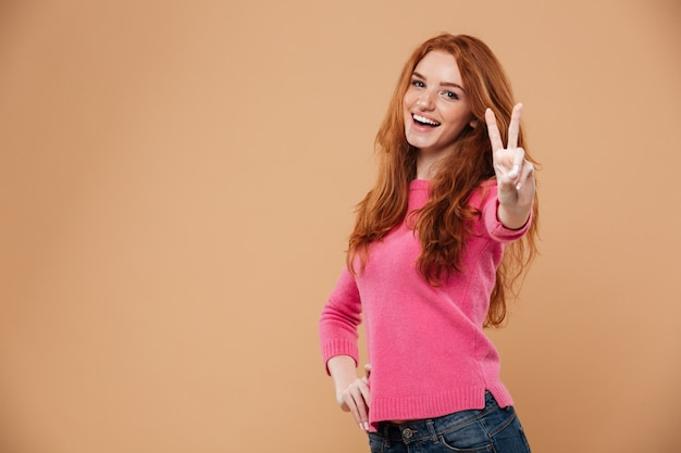 Portrait of a young attractive redhead girl with victory hand gesture Free Photo