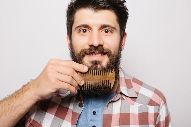 Ritratto di giovane maschio attraente hipster rossa con sguardo serio e fiducioso, tenendo il pettine di legno e facendo la sua folta barba. elegante barbiere barbuto in camicia a scacchi pettinatura in salone. orizzontale Foto Gratuite