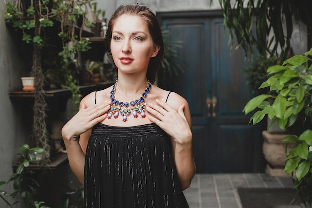 Portrait of young attractive woman in elegant black dress wearing luxury rich necklace jewelry, summer style, fashion trend, vacation, stylish accessories, posing on tropical villa on bali Free Photo