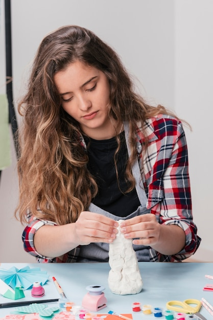 Portrait of young attractive woman making craft object using white clay Free Photo
