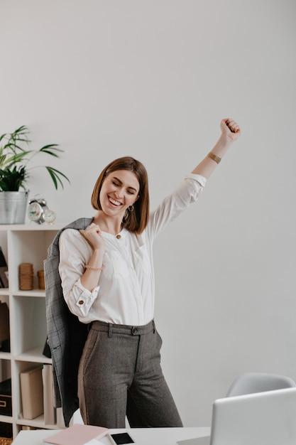 Il ritratto di giovane donna attraente in attrezzatura dell'ufficio gode del successo aziendale contro il posto di lavoro luminoso. Foto Gratuite