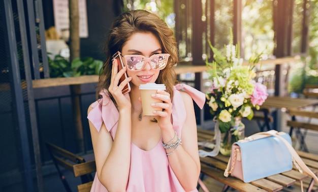 Ritratto di giovane donna attraente seduta in un bar, vestito di moda estiva, stile hipster, vestito di cotone rosa, occhiali da sole, sorridente, bere caffè, accessori eleganti, abbigliamento alla moda, parlando al telefono Foto Gratuite