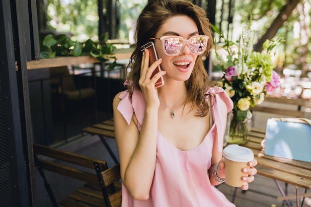 Portrait of young attractive woman sitting in cafe, summer fashion outfit, pink cotton dress, sunglasses, smiling, drinking coffee, stylish accessories, trendy apparel, talking on phone Free Photo