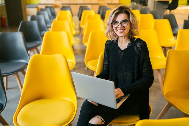 Portrait of young attractive woman sitting in lecture hall working on laptop wearing glasses, student learning in classroom with many yellow chairs Free Photo
