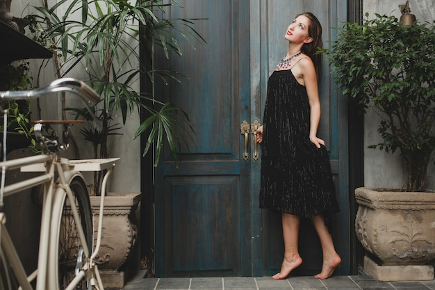 Portrait of young attractive woman in stylish black dress posing at tropical villa, sexy, elegant summer style, fashionable necklace accessories, smiling, romantic mood, luxury Free Photo