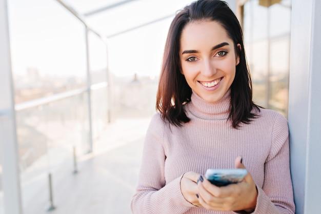 シティービューのテラスで晴れた朝に笑顔ブルネットの髪を持つ肖像若い魅力的な女性。積極性を表現する若い女性。 無料写真