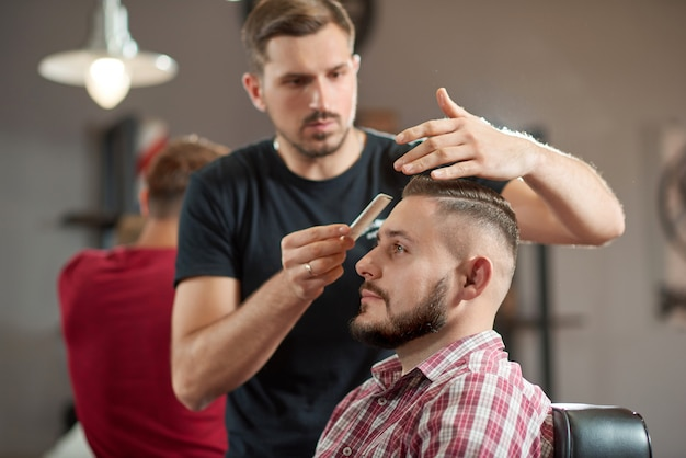 Portrait of a young barber styling hair of his bearded client. Free Photo