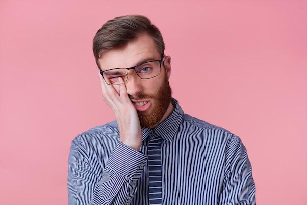 Ritratto di giovane uomo d'affari barbuto indossa occhiali si sente infelice e stanco, puntellando la testa, isolato su sfondo rosa. Foto Gratuite