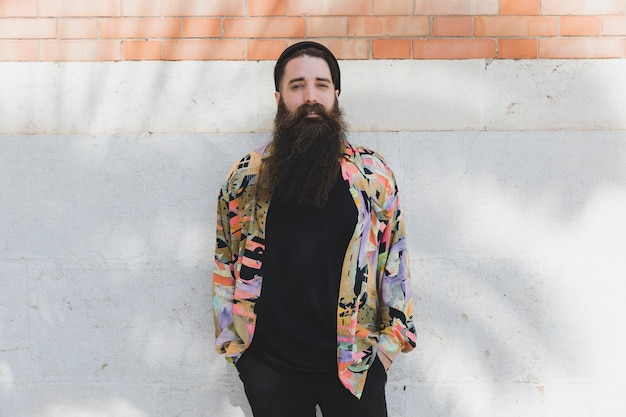 Portrait of a young bearded man standing against white wall Free Photo