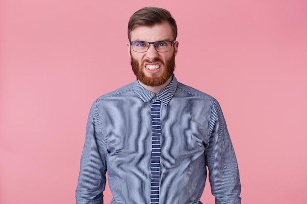 Ritratto di giovane uomo barbuto in una camicia a righe con gli occhiali, arrabbiato e mostra aggressivamente i denti isolati su sfondo rosa. Foto Gratuite