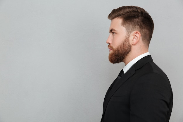 Portrait of a young bearded man in suit looking forward Free Photo