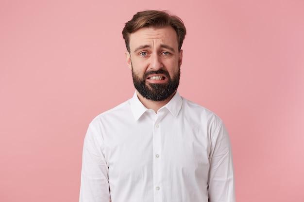 蜘蛛を見た肖像画の若いひげを生やした男。ピンクの背景の上に孤立した嫌悪感で見えます。 無料写真