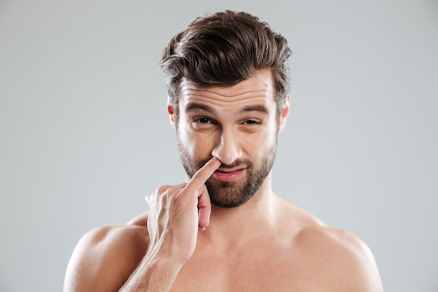 Portrait of a young bearded naked man picking his nose Free Photo