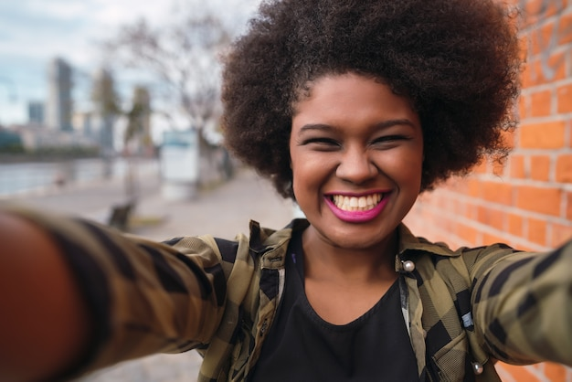Portrait of young beautiful afro american woman taking a selfie outdoors in the street. Free Photo