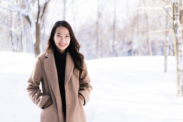 Portrait young beautiful asian woman smile happy travel and enjoy with snow winter season Free Photo