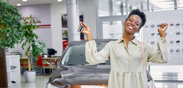 Portrait of young and beautiful black woman with keys from her new car Premium Photo