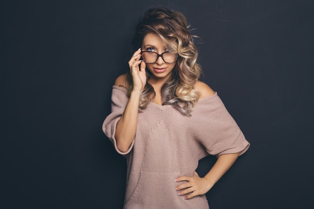 Portrait of a young beautiful blond-haired wearing trendy glasses and casual clothes and posing over black background Free Photo