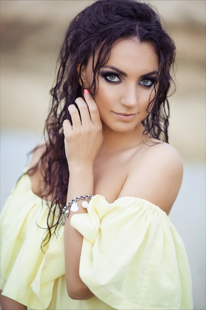 Portrait of young beautiful brunette girl with wet hair in yellow dress. Premium Photo