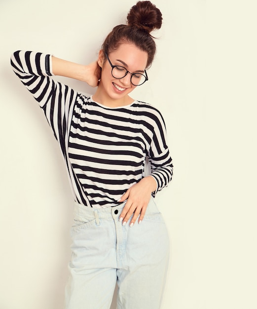 Portrait of young beautiful brunette woman girl model with nude makeup in glasses in summer hipster clothes posing near wall. Free Photo