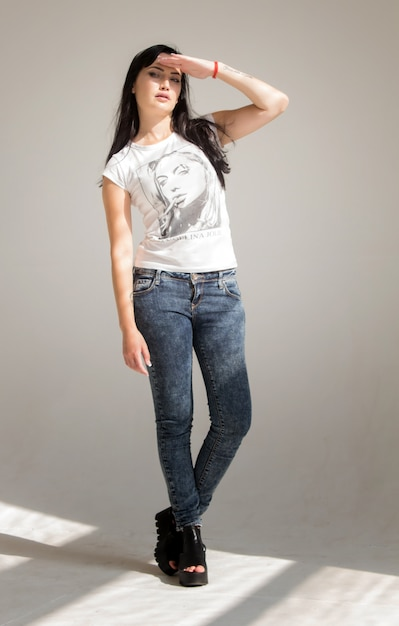 Portrait of a young beautiful brunette woman in a white t-shirt and jeans Premium Photo