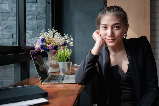 Portrait of young beautiful business woman sitting in the co-working space. Premium Photo