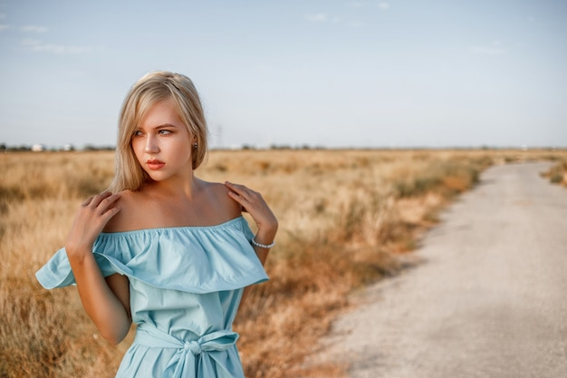 Portrait of a young beautiful caucasian blonde girl in a light blue dress standing on a field with sun-dried grass next to a small country road Premium Photo