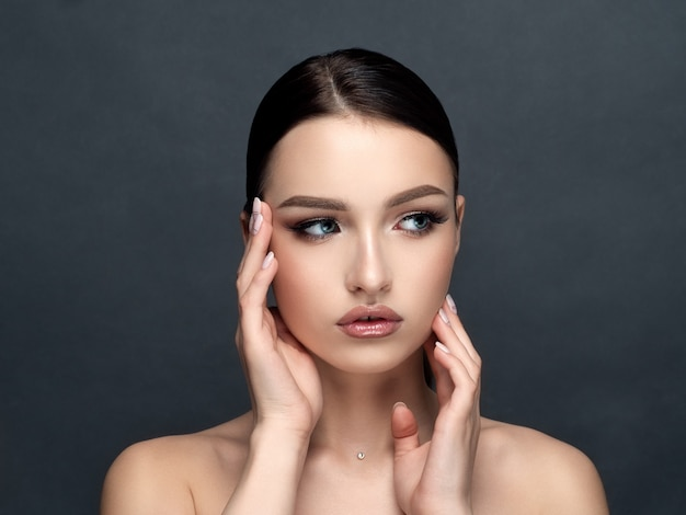 Attractive young woman touching her face sensually