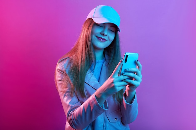 Portrait of young beautiful fashionable model wearing leather baker and baseball cap, holding smart phone in hands Free Photo
