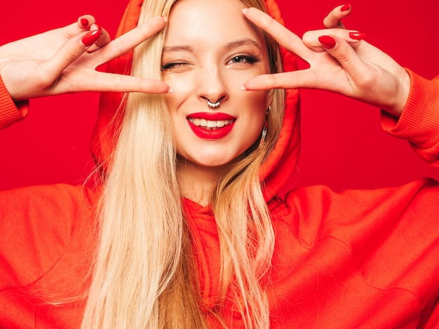 Portrait of young beautiful hipster bad girl in trendy red  hoodie and earring in her nose.  positive model shows peace sign Free Photo