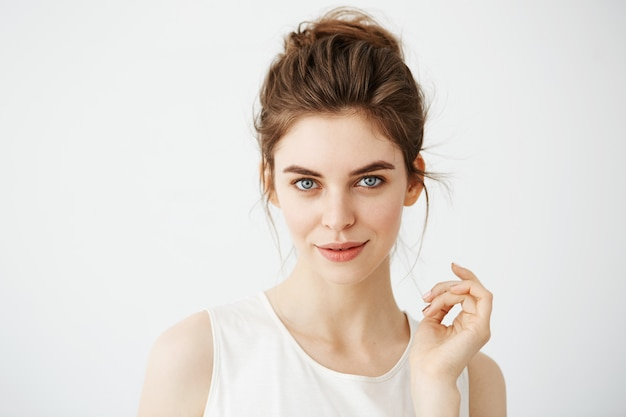 Portrait of young beautiful playful woman with bun posing. Free Photo