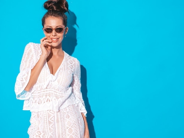 Portrait of young beautiful sexy smiling woman with ghoul hairstyle. trendy girl in casual summer white hipster suit clothes in sunglasses. hot model isolated on blue Free Photo
