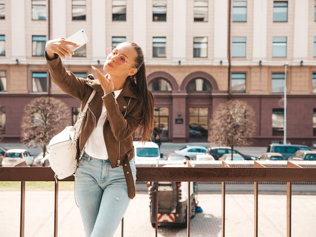 Portrait of young beautiful smiling girl in summer hipster jacket and jeans.model taking selfie on smartphone.woman making photos in the street.in sunglasses. gives air kiss Free Photo