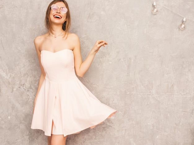 Portrait of young beautiful smiling girl in trendy summer light pink dress. sexy carefree woman posing. positive model having fun. dancing in round sunglasses Free Photo