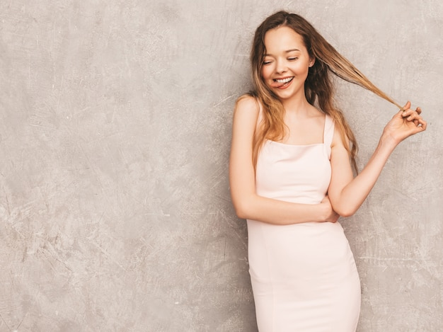 Portrait of young beautiful smiling girl in trendy summer light pink dress. sexy carefree woman posing. positive model having fun Free Photo