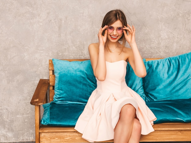 Portrait of young beautiful smiling girl in trendy summer light pink dress. sexy carefree woman sitting on bright blue sofa. posing in luxury interior Free Photo