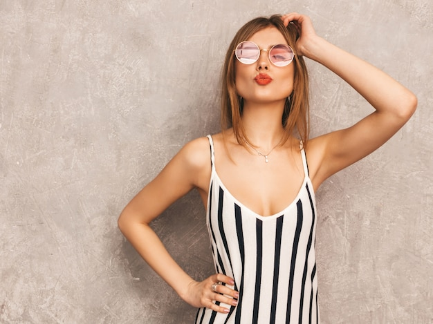 Portrait of young beautiful smiling girl in trendy summer zebra dress. sexy carefree woman posing. positive model having fun in round sunglasses. giving kiss Free Photo
