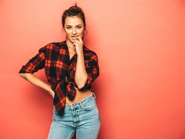 Portrait of young beautiful smiling hipster girl in trendy summer checkered shirt and jeans clothes. sexy carefree woman posing near pink wall in studio. positive model with no makeup Free Photo