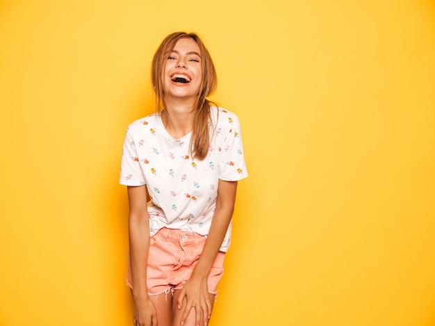 Il ritratto di giovane bella ragazza sorridente dei pantaloni a vita bassa negli shorts d'avanguardia dei jeans dell'estate copre. donna spensierata sexy che posa vicino alla parete gialla. divertimento del modello positivo Foto Gratuite
