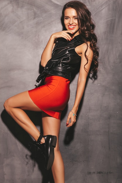 Portrait of young beautiful smiling hipster woman in trendy summer red skirt and black leather jacket. sexy carefree woman posing near wall. brunette model with makeup and hairstyle Free Photo