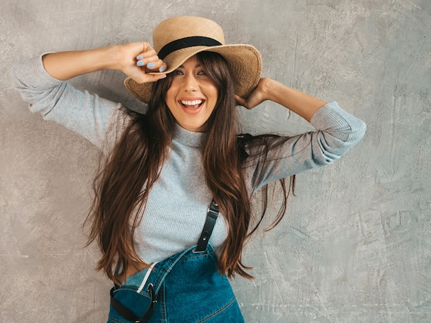 Portrait of young beautiful smiling woman looking . trendy girl in casual summer overalls clothes and hat. Free Photo