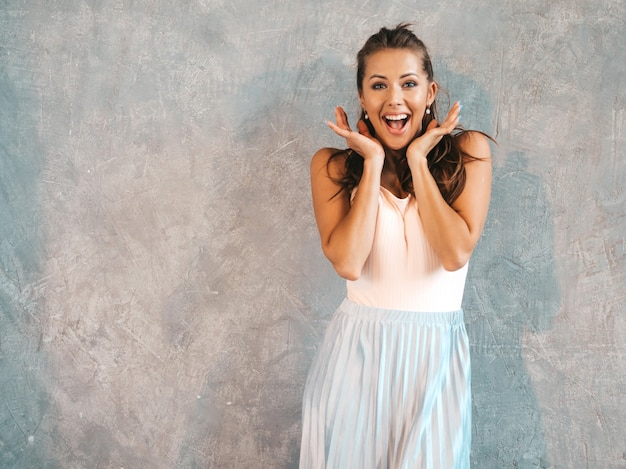 Portrait of young beautiful surprised woman looking  with hands near face. trendy girl in casual summer clothes. shocked female posing near gray wall Free Photo