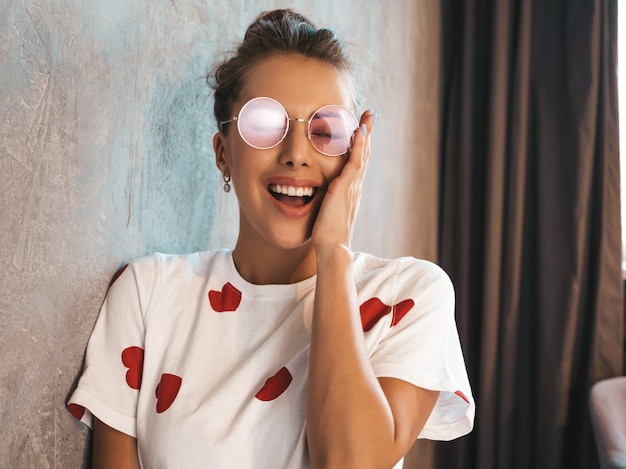 Portrait of young beautiful surprised woman with hands near face  trendy girl in casual summer clothes  shocked female posing near gray wall in the interior in studio  in sunglasses Free Photo