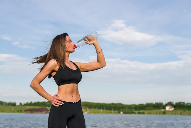Portrait of young beautiful woman drinking water at summer green park. Free Photo