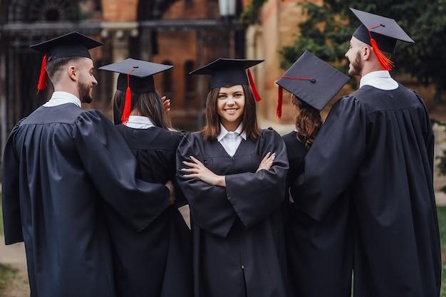 肖像画の若い美しい女性は教育を終え、彼女は黒いマントを着ています。 Premium写真