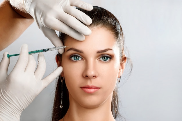 Portrait of a young, beautiful woman getting botox cosmetic injection Premium Photo