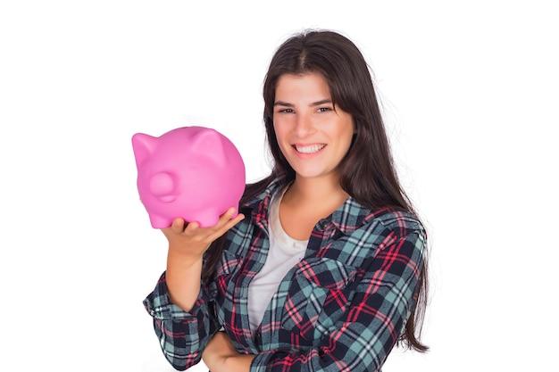 Ritratto di giovane bella donna che tiene un salvadanaio in studio. risparmia il concetto di denaro. Foto Gratuite