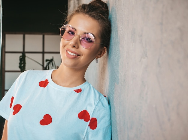 Portrait of young beautiful woman looking at camera  trendy girl in casual summer white t-shirt and sunglasses  funny and positive female posing near gray wall in studio Free Photo